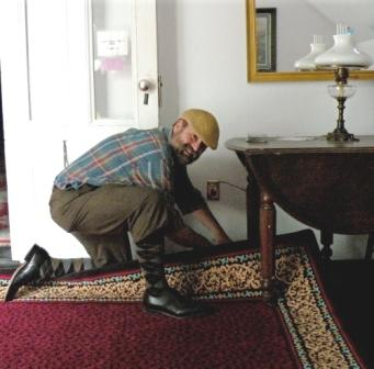 John Burrows inspects new carpet.